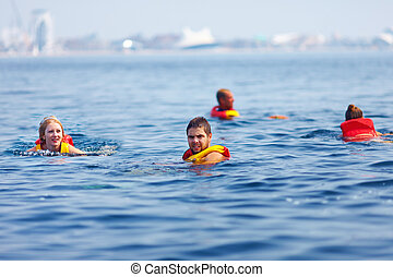 people in lifejackets swimming in open sea - people in life...