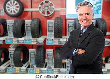 Car dealer. - Car dealer man over tire tire background. Auto...