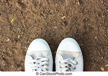 White shoes walking on soil top view.