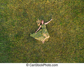 Aerial view of young woman in a green dress lie down on a...