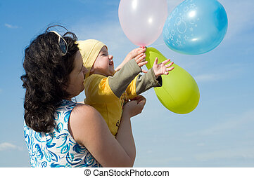 Baby with ballons - A baby is holding ballons