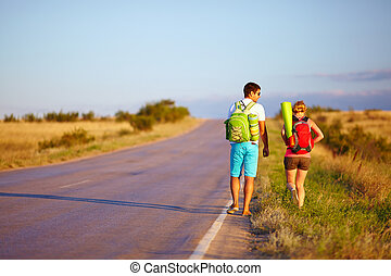 young people traveling hitchhiking. summer field