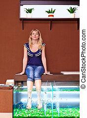young girl taking fish pedicure treatment, rufa garra spa...