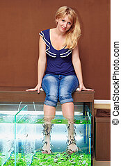 young girl taking fish pedicure treatment, rufa garra spa...