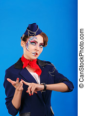 Stewardess with face art considers fingers. Young attractive...