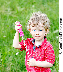 boy and soap bubbles - The little boy puts soap bubbles on...