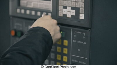 Professional industrial engineer adjusting modern machine settings CNC punching machine.