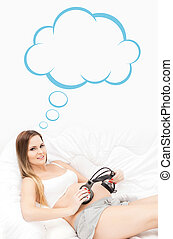 Beautiful pregnant woman putting headphones on her abdomen with thinking cloud concept.