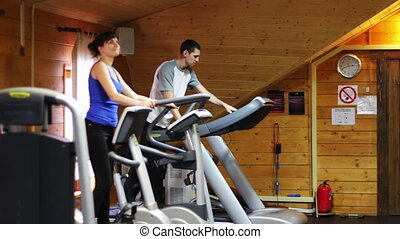The girl and the guy in the gym - The girl is engaged in...