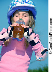 drinking sporty child - child with protective helmet and...