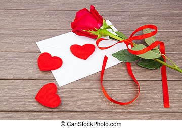 Romantic love letter with red rose on wooden