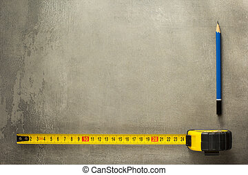 tape measure and pencil on old texture