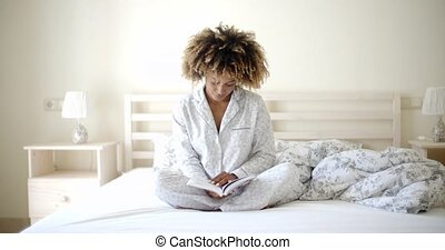 Woman Reading A Book On Bed - Woman reading a book on his...