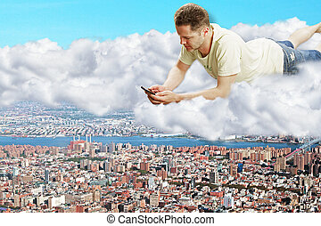 A man with smartphone laying on clouds above the megapolis city