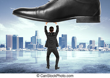 Business pressure concept with businessman under the boot at...
