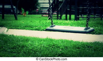 scary empty swing with chains swaying at playground for child, moved from wind, on green meadow background, scary style theme in slow motion loopable, hd 1080p