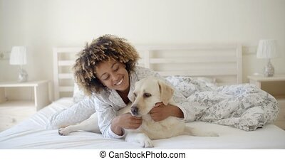 Woman Is Holding A Dog On A Bed - Young woman is holding a...