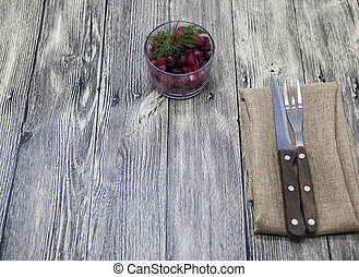 Beet salad salad in a glass vase with fork and knife on a...