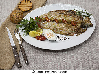 Fried fish whitefish on plate with vegetables and bread with...