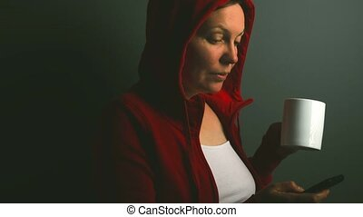Beautiful red hooded woman drinking cup of coffee, sending...
