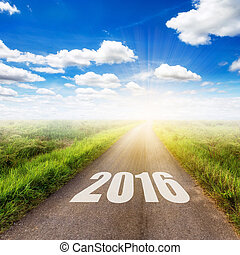 country road and field and blue sky with white clouds. Forward to the New Year 2016.