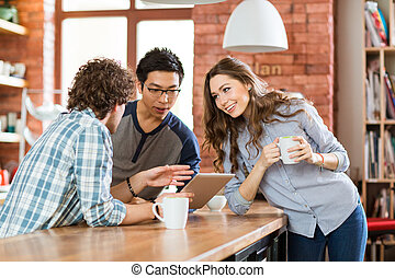 Group of joyful positive students using laptop in cafe