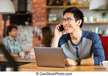 Positive asian man using laptop and talking on cellphone -...