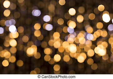 Abstract glittering lights, gold background, a real foto in...