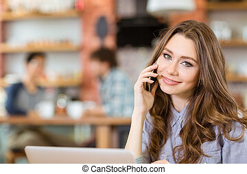 Beautiful positive young woman talking on cellphone