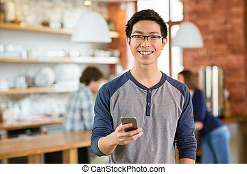 Young smiling asian boy in glases using smarphone - Young...