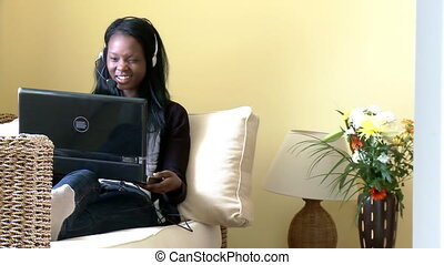 Smiling woman using a laptop with headset on lying on sofa