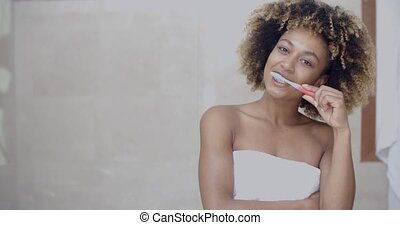 Teeth Cleaning At Home - Black woman brushing her teeth and...