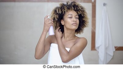 Woman Using Hair Spray In Bathroom - Young woman in towel...