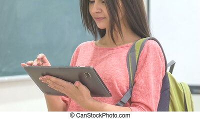 Young female student texting on her tablet. - Amusing...