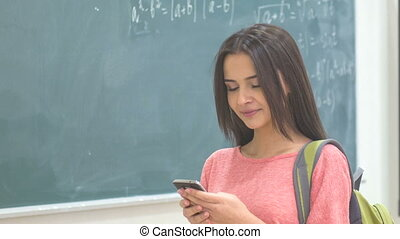 Young female student texting on her smartphone. - Amusing...