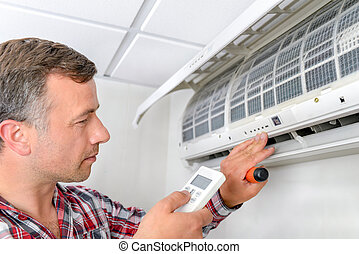 Man checking air conditioning unit