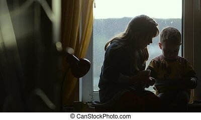 Children sitting on the windowsill with smartphone and book