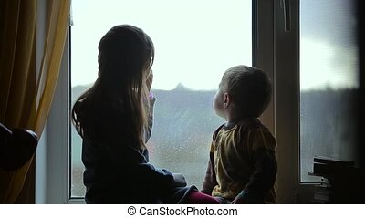 Children sitting on the windowsill and look out