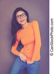 Stretching her new jeans. Beautiful young woman in eyeglasses stretching her jeans and smiling while standing against grey background