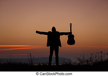 Man with guitar in sunset - Man standing with guitar in...