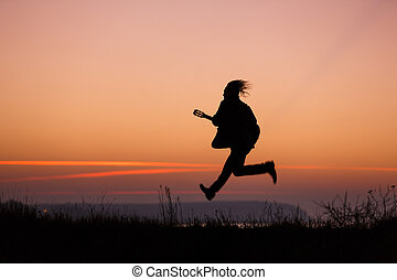 Man jumping with guitar - Happy man jumping with guitar in...
