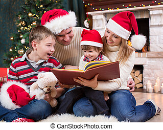 Family reading a book in front of Christmas tree