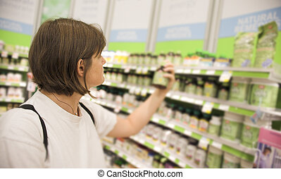 drugstore - woman shopping and looking at health products in...