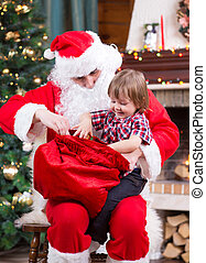 Santa Claus pulls a present out sack to child near the fireplace and Christmas tree at home