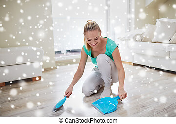 happy woman with brush and dustpan sweeping floor - people,...