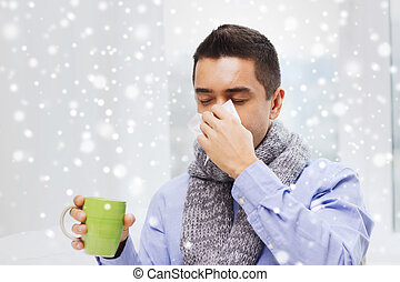 ill man with flu drinking tea and blowing nose - healthcare,...