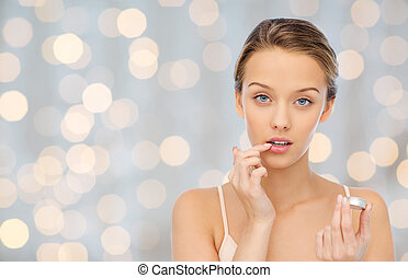 young woman applying lip balm to her lips