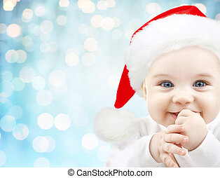 happy baby in santa hat over blue holidays lights -...