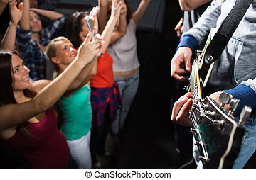 close up of people at music concert in night club -...