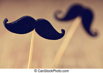felt mustaches in sticks, filtered - closeup of two...